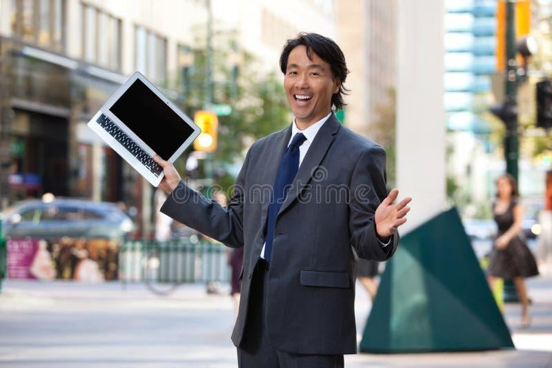 Ordinateur portatif et rire de fixation d'homme d'affaires images libres de droits