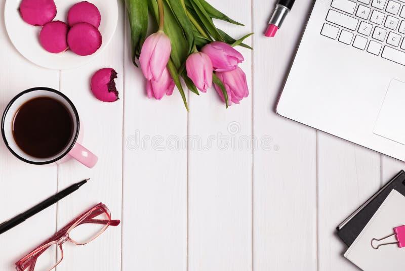 Ordinateur, verres, café et accessoires dans la couleur rose sur le blanc image stock