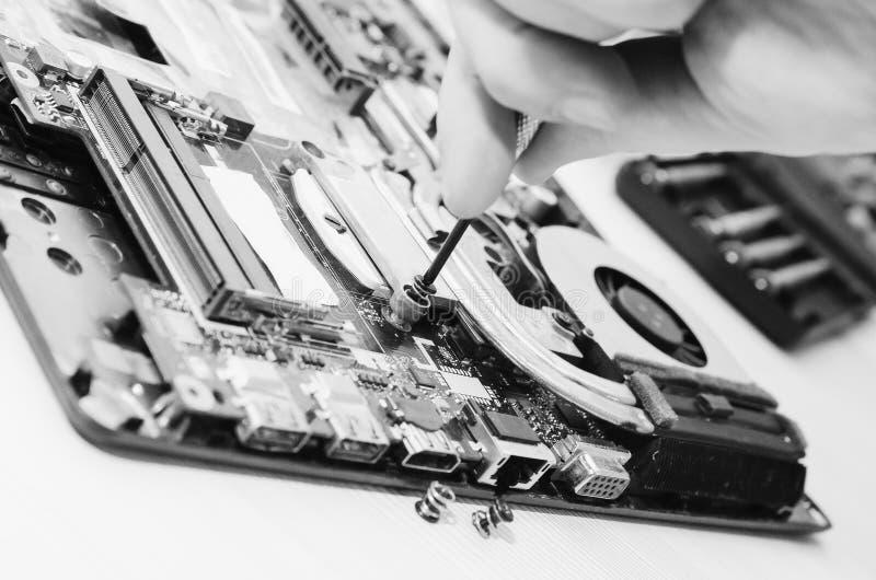 Ordinateurs portables de réparation, plan rapproché des mains et vieil ordinateur démantelé Ð'lack et photographie blanche photos libres de droits