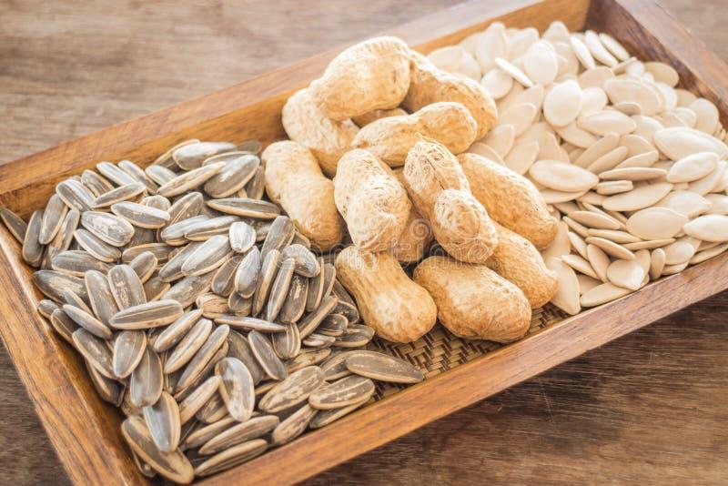Ordinato di interi girasole, arachide e zucca del grano su di legno fotografie stock libere da diritti