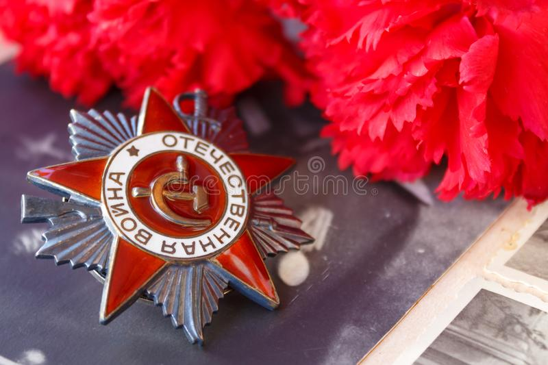 Ordine sovietico della guerra patriottica dell'iscrizione patriottica di guerra con i garofani rossi contro lo sfondo di vecchie  fotografie stock libere da diritti