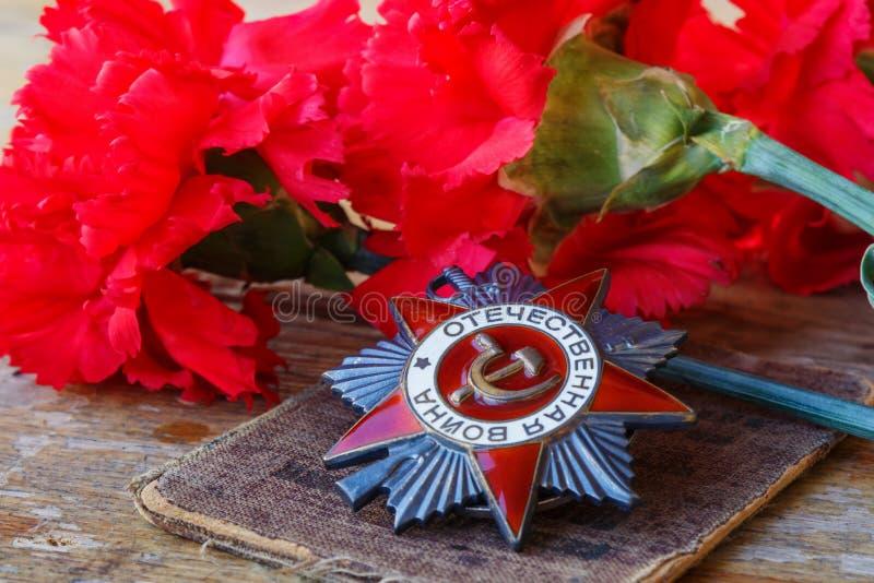 Ordine sovietico della guerra patriottica dell'iscrizione patriottica di guerra con i garofani rossi su una vecchia tavola di leg fotografia stock