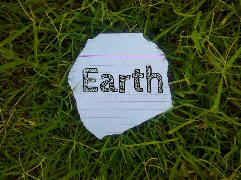 Ordjorden som är skriftlig på stycket av papper på gräset arkivfoto