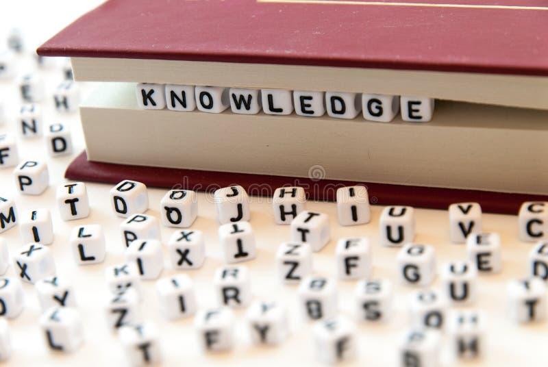 Ordkunskap som är skriftlig med bokstäver mellan en bok, söker vit bakgrund med bokstäver fördelade runt om läs- begrepp för utbi royaltyfria foton