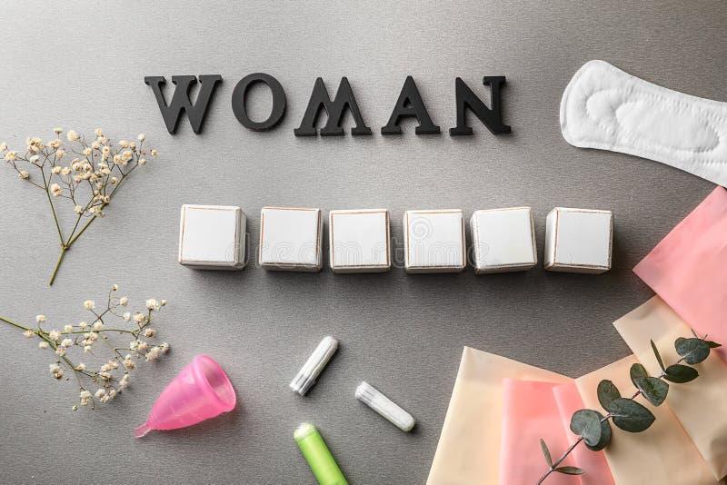 OrdKVINNA som göras av mörka bokstäver med tomma kuber och kvinnliga hygienobjekt på grå bakgrund fotografering för bildbyråer