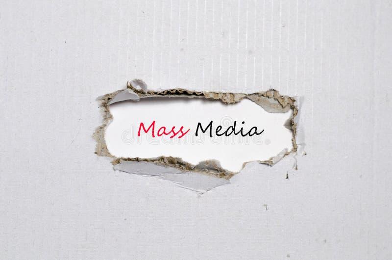 Ordmassmedia som visas bak sönderrivet papper fotografering för bildbyråer