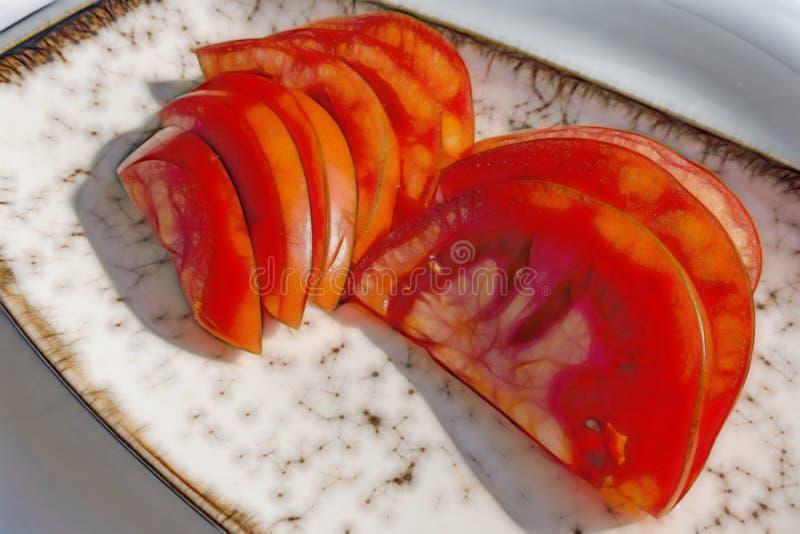 Ordna till för att äta skivade tomater i platta arkivfoto