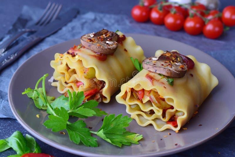 Ordna till för att äta vegetariska lasagner i rullar med champinjoner, paprika, oliv, tomatsås på en brun keramisk platta Sunt fotografering för bildbyråer