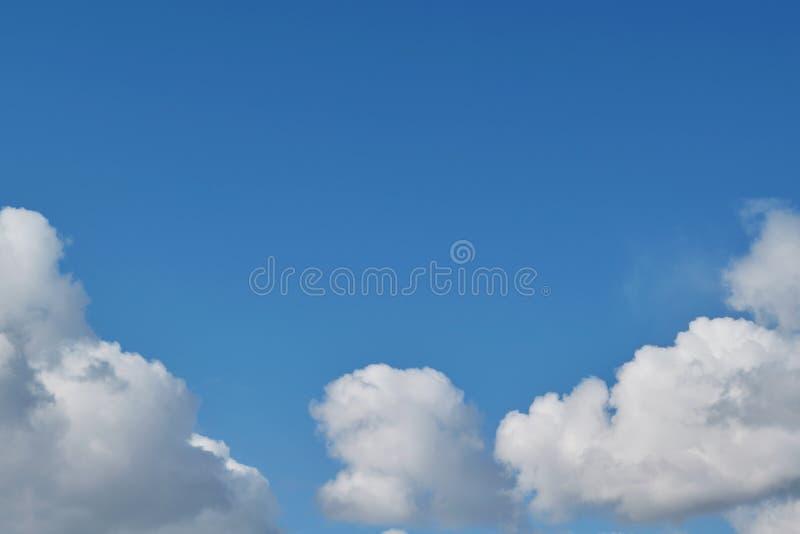 Ordnade fluffiga vita stackmolnmoln för blåa himlar i form av en båge royaltyfria foton