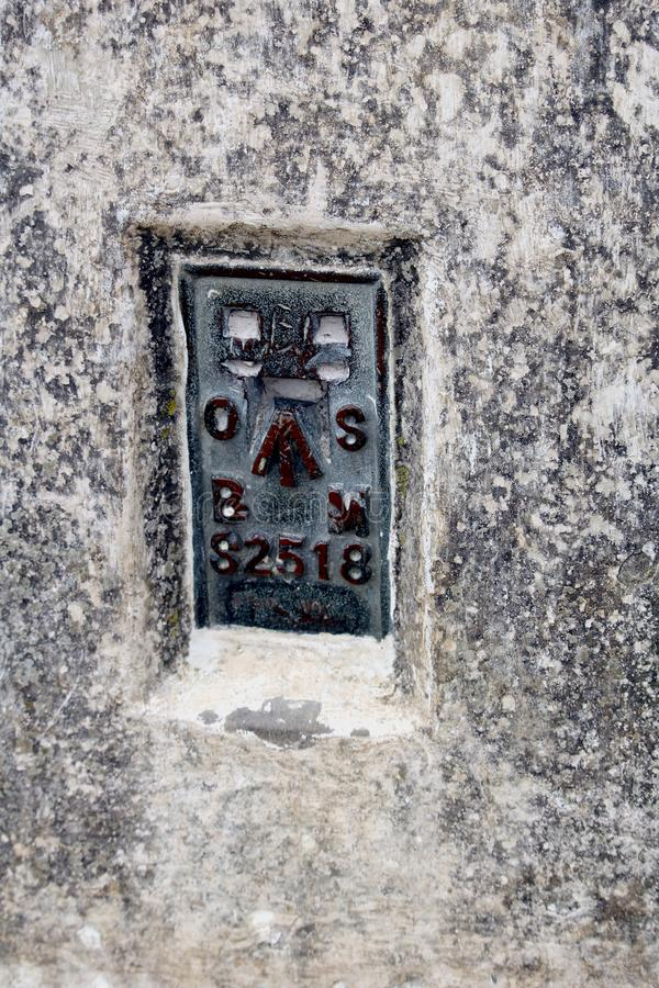 The Ordnance Survey Bench Mark on the side of a British triangulation point, or Trig Point royalty free stock images
