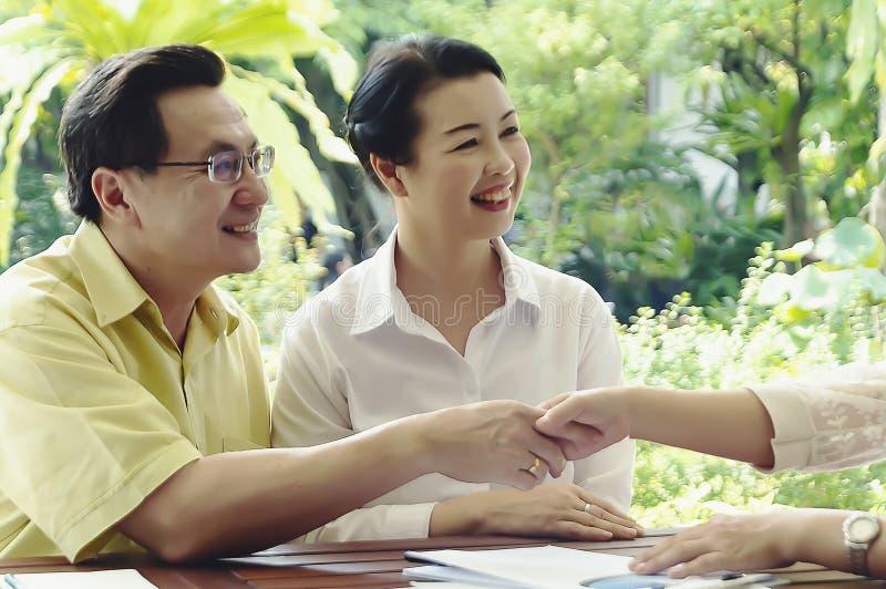 Ordnar till den finansiella konsulenten för det höga parmötet för investering, äldre klienter för att köpa den konsulterande mäkl fotografering för bildbyråer