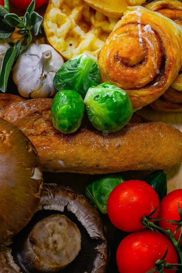 Ordningen av olika bröd och grönsaker är fortfarande, cinnamaorulle, vitlök, Bryssel spirar, tomatfokusen på Bryssel groddar arkivbilder