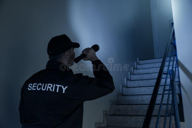 Ordningsvakt Searching On Stairway med ficklampan arkivbild