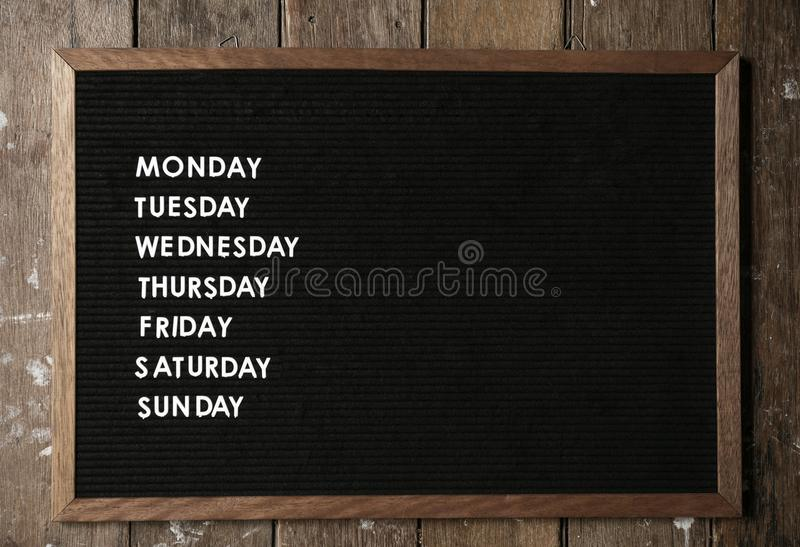 Ordre du jour sur le conseil noir sur le mur en bois photos stock