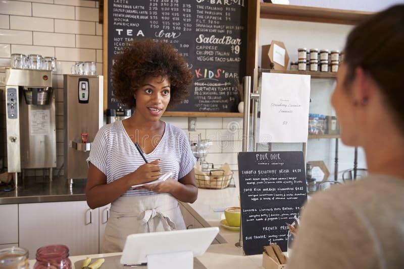 Ordre du ½ s de ¿ de customerï d'écriture de serveuse au compteur du café images stock