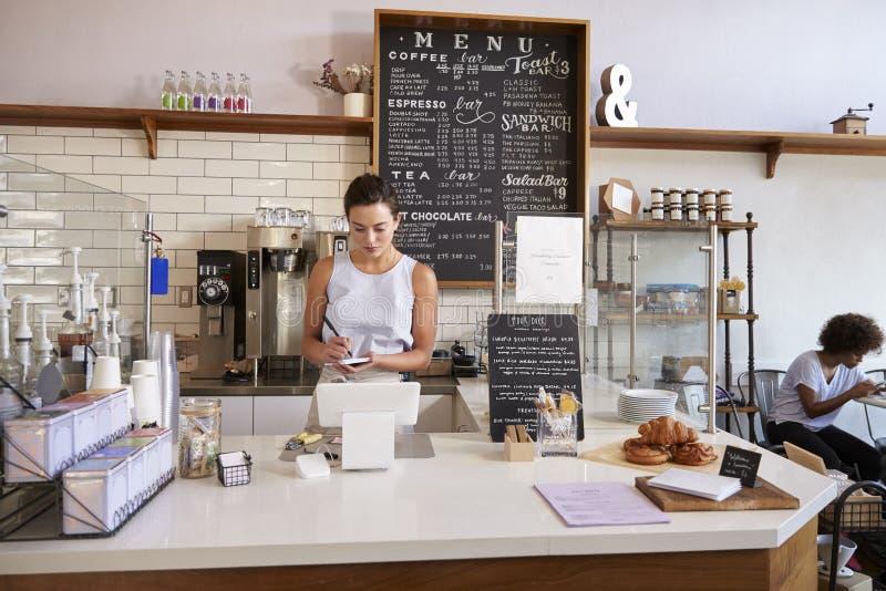 Ordre du ½ s de ¿ de customerï d'écriture de serveuse au compteur du café photographie stock libre de droits