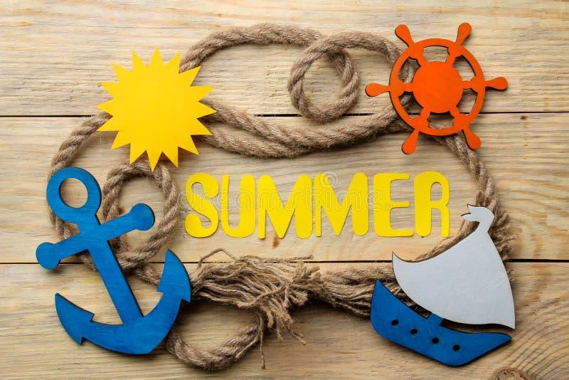 Ordsommar av pappers- gula bokstäver och repflottan och marin- tillbehör på en naturlig träbakgrund Sommar semester relax arkivfoto