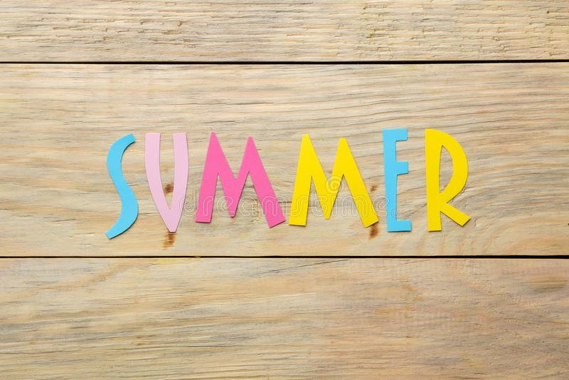Ordsommar av pappers- mångfärgade bokstäver på en naturlig träbakgrund Sommar semester avkoppling Top besk?dar royaltyfria foton