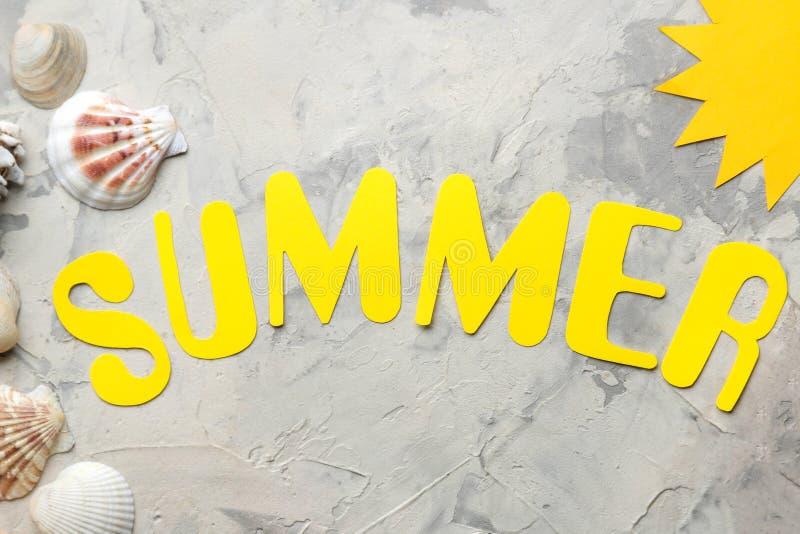 Ordsommaren av pappers- gula bokst?ver och havstillbeh?r, skal p? en ljus konkret bakgrund Sommar semester avkoppling fotografering för bildbyråer
