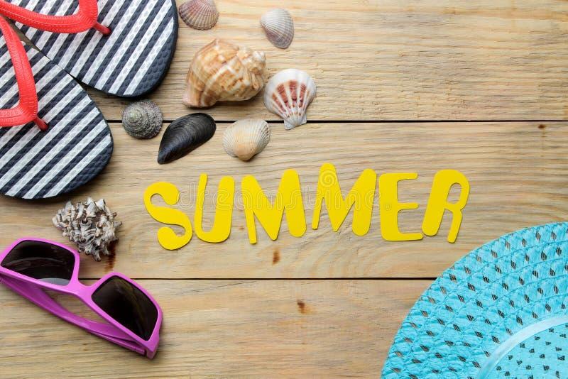 Ordsommaren som göras av pappers- gula bokstäver, och sommar, strandtillbehör på en naturlig träbakgrund Sommar semester relax arkivfoto