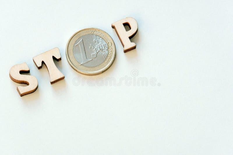 Ordstoppet som är skriftligt på en vit bakgrund i trälatinska bokstäver och ett mynt ett euro kopiera avst?nd Bakgrundsvit arkivfoto