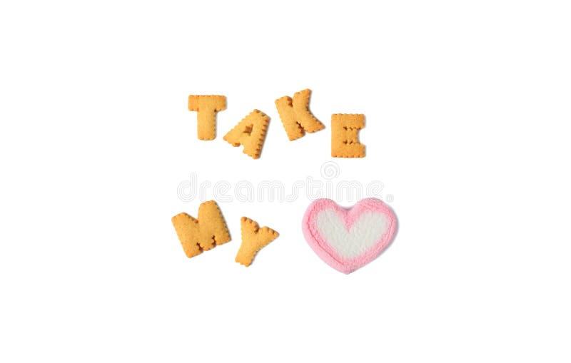 OrdTAGANDET MIN HJÄRTA som stavades med alfabet, formade kakor och en hjärta formad marshmallowgodis på vit bakgrund royaltyfri foto
