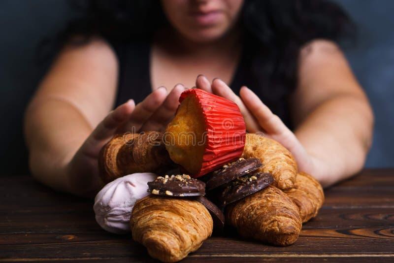 Ordures de jeune femme mangeant de la nourriture industrielle photographie stock libre de droits