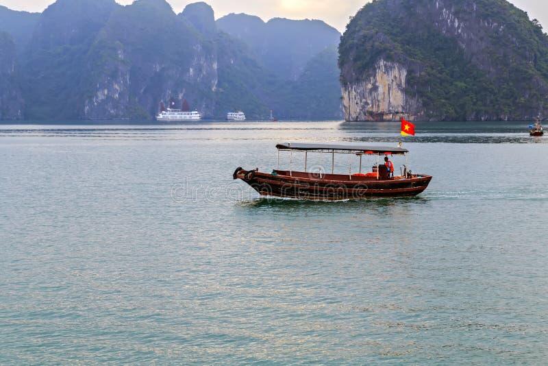 Ordures de touristes de bateau de touristes flottant la baie de Halong de roches de chaux au Vietnam image stock