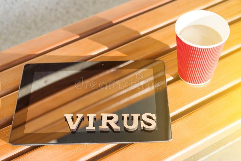OrdVIRUS med trätappningbokstäver, bakgrundsminnestavla på träbänken, kopp kaffe fotografering för bildbyråer