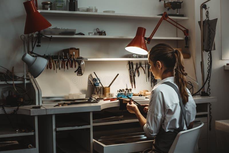 Ore di lavoro lunghe Punto di vista posteriore di giovane gioielliere femminile che fa nuovo prodotto alla sua officina dei gioie immagini stock