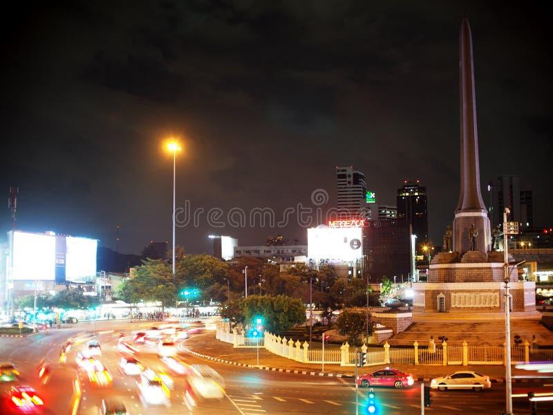 Ore di punta di sera le vie e la via intorno ad un hub importante di trasporto alla giunzione del MONUMENTO di VITTORIA, BANGKOK immagine stock libera da diritti