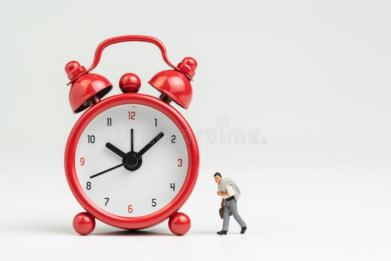 Ore lavorative, tempo andare lavorare o concetto di programma della riunione, figura miniatura uomo d'affari con il vestito e val immagini stock