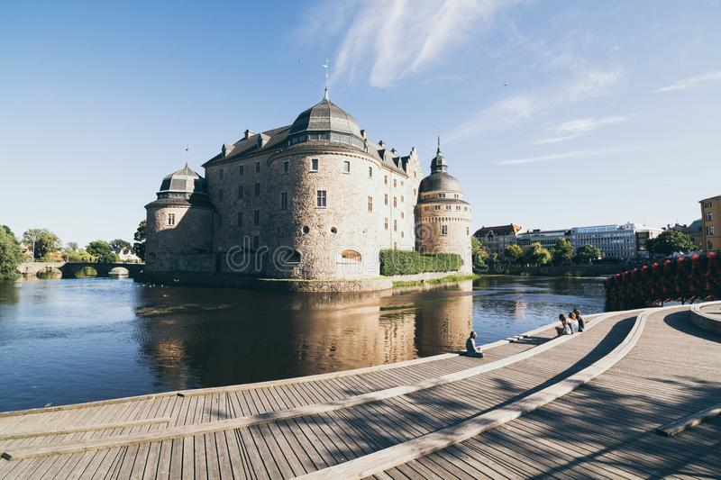 Orebro, Sweden - August 2017: people relaxing in front of ancient Orebro castle. At sunset, unesco, tower, city, wall, town, old, historical, history, swedish royalty free stock image
