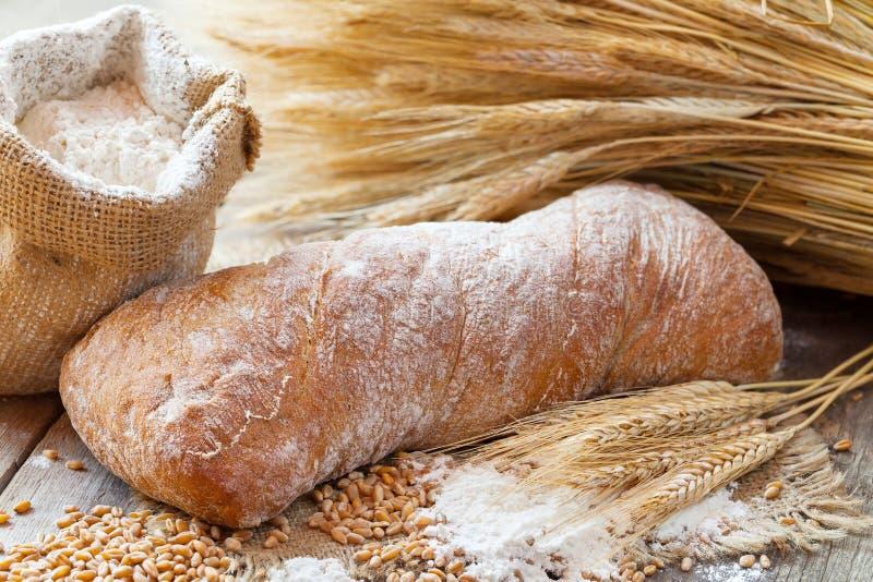Orecchie del pane fresco, della farina e del grano sulla tavola di legno immagine stock