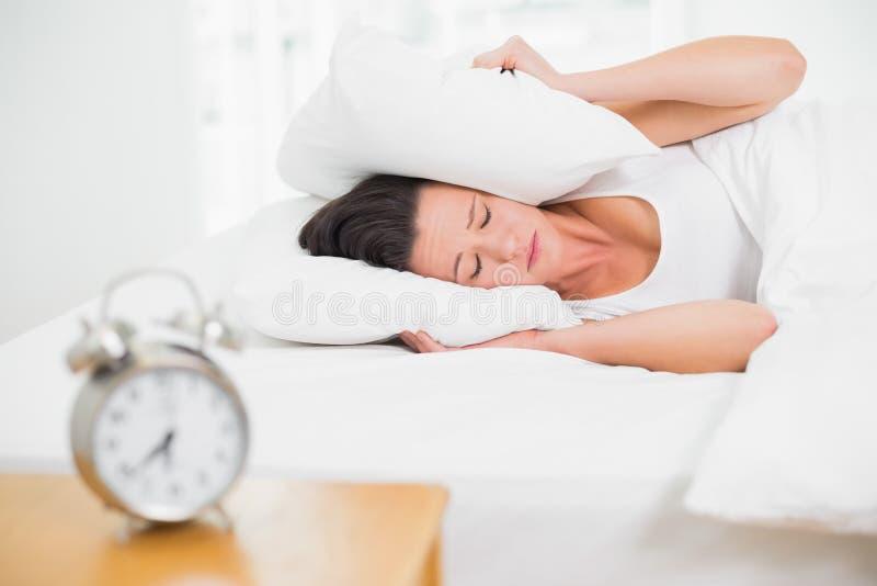 Orecchie della copertura della donna con il cuscino e la sveglia sulla tavola laterale fotografia stock libera da diritti