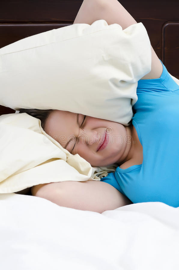 Orecchie della copertura della giovane donna con il cuscino fotografie stock