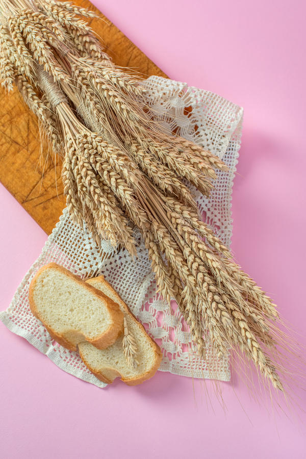 Orecchie delle fette biscottate del pane bianco e del grano su un bordo di legno da sopra fotografia stock