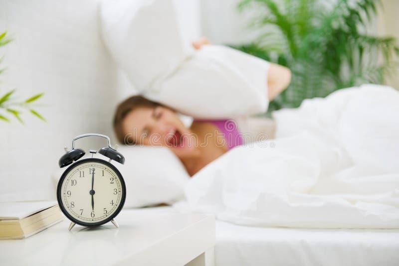 Orecchie di chiusura della ragazza dal cuscino per evitare l'orologio di udienza fotografia stock libera da diritti