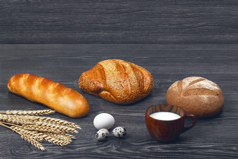Orecchie di grano, uova di quaglia e del pollo, bicchiere di latte, di recente pane al forno e una pagnotta su fondo di legno fotografia stock