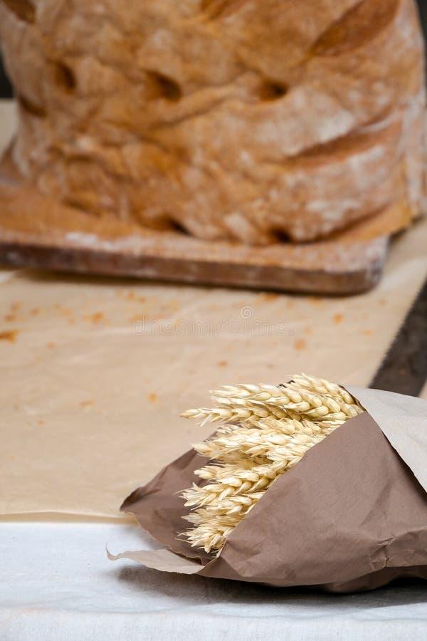 Orecchie dorate del grano avvolte in carta del mestiere e pagnotta di intero pane rustico del grano immagini stock libere da diritti