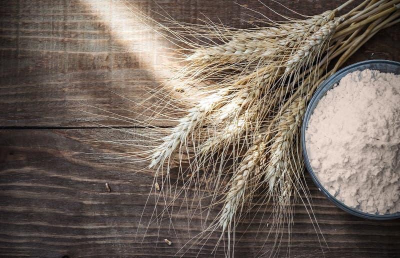 Orecchie e farina asciutte del grano del fondo sulla vecchia tavola di legno fotografia stock