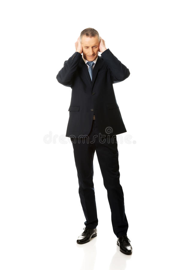 Orecchie stanche integrali della copertura dell'uomo con le mani fotografia stock