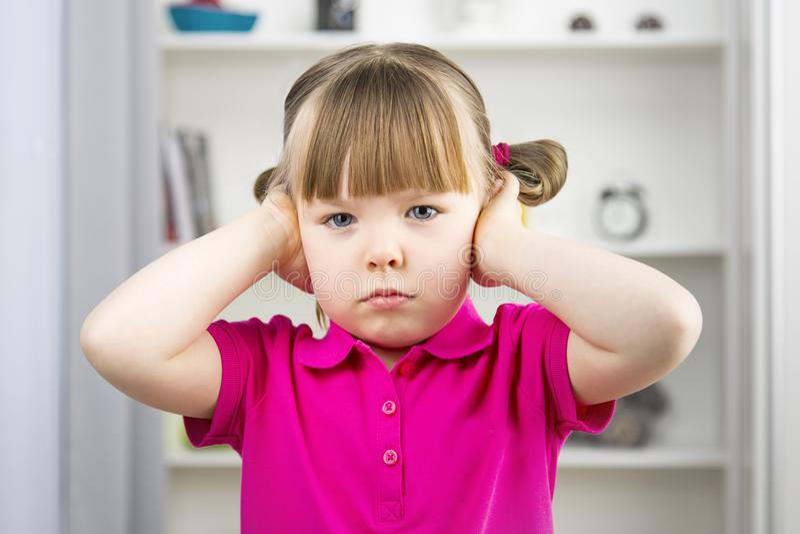Orecchie sveglie della copertura della bambina con le mani fotografia stock libera da diritti