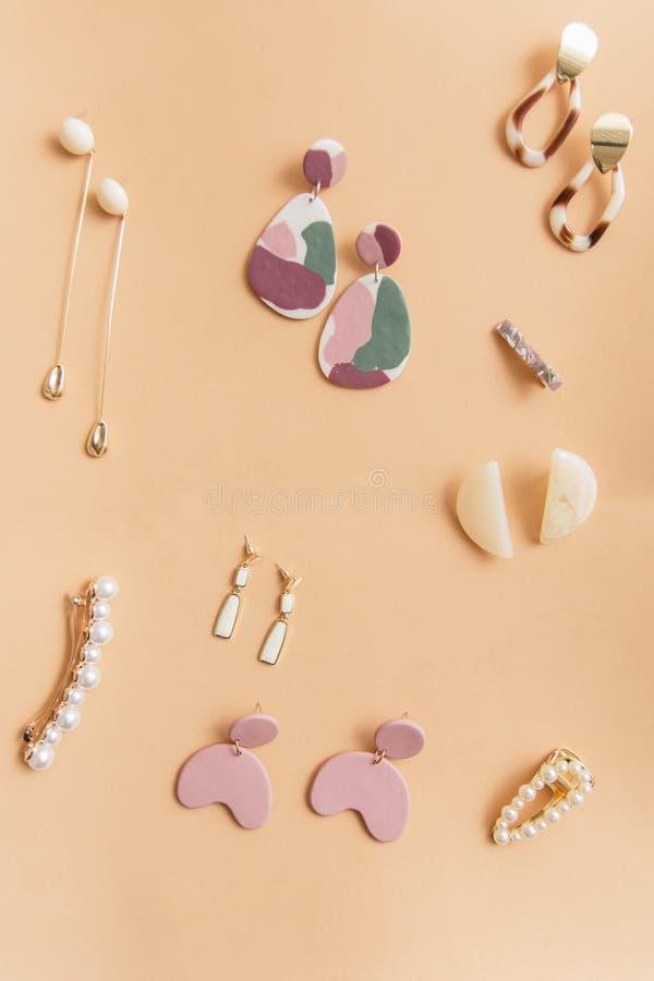 orecchini alla moda moderni dell'oro su un fondo beige orecchini differenti su un fondo normale fotografia stock libera da diritti