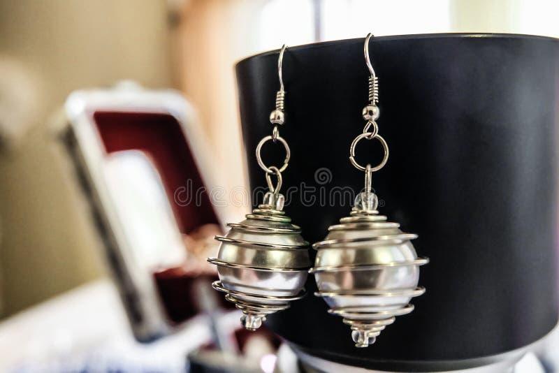 Orecchini argentei della perla con fatto a mano a spirale d'acciaio immagine stock