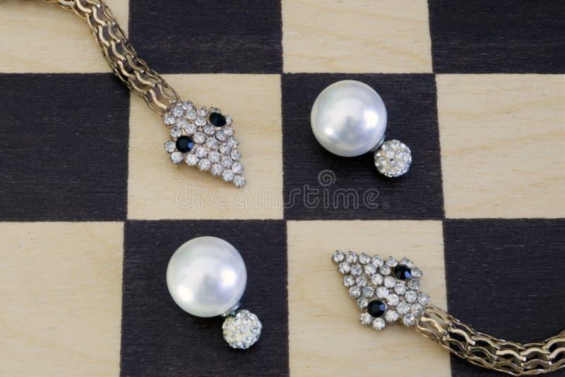 Orecchini bianchi con i cristalli e gioielli sotto forma di serpenti fotografie stock