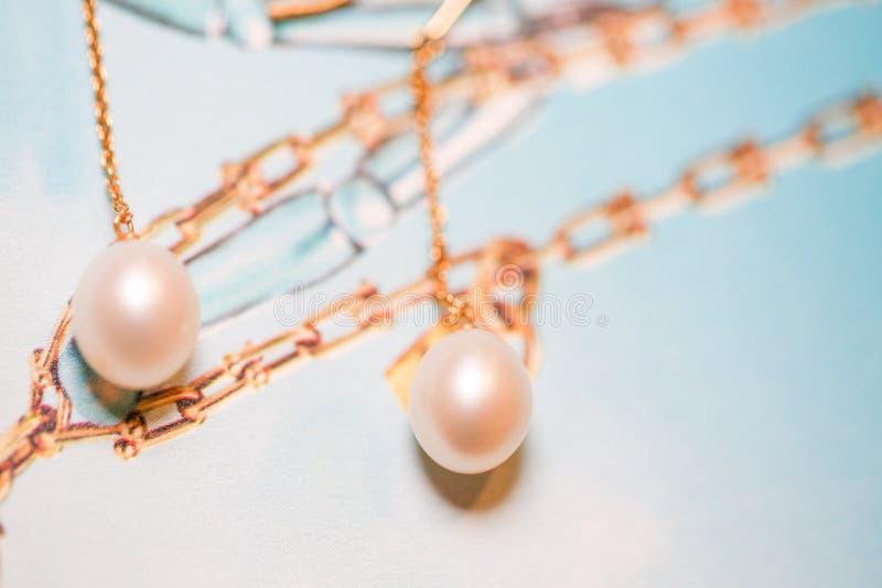 Orecchini bianchi dell'oro della perla vicino su fotografia stock