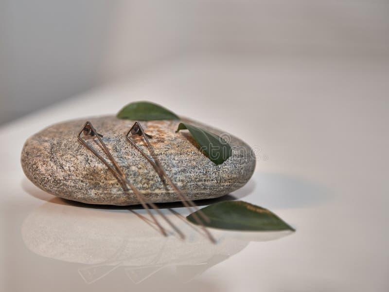 Orecchini d'argento sulla pietra del granito fotografia stock