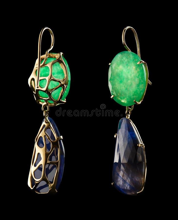 Orecchini dell'oro con le pietre preziose naturali verdi e blu sul nero immagine stock
