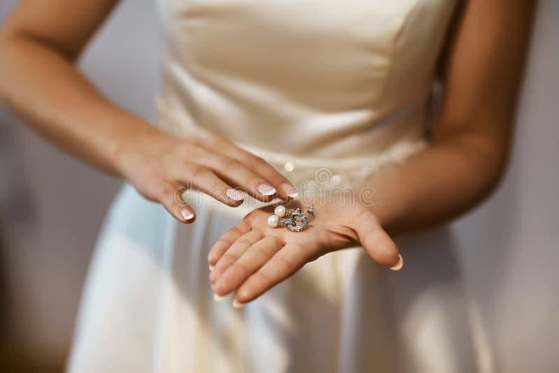 Orecchini di nozze su una mano nuziale, accessori di mattina e dei gioielli del ` s della sposa e concetto della decorazione fotografia stock libera da diritti